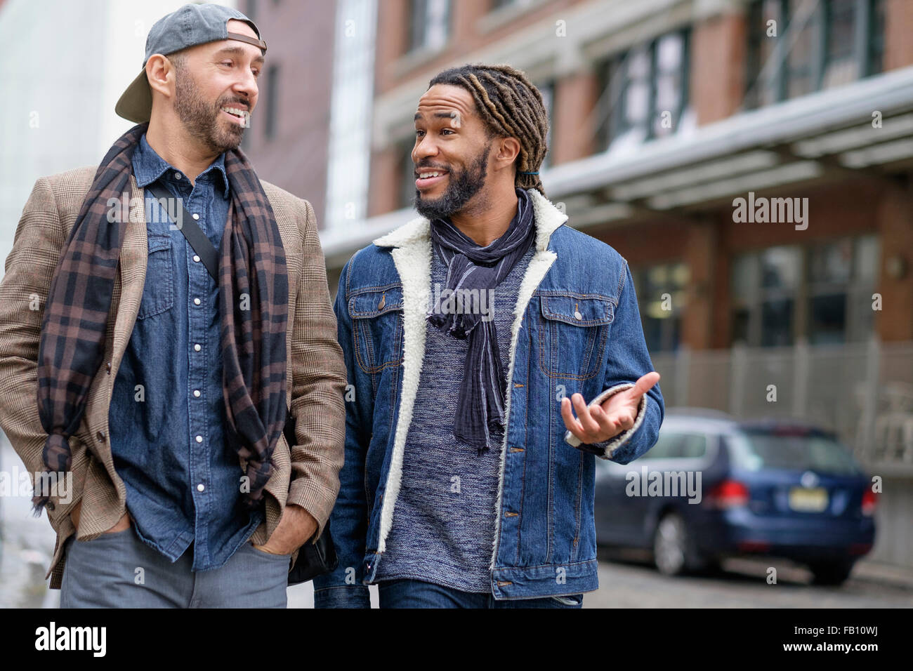 Smiley homosexual couple walking down street - Stock Image
