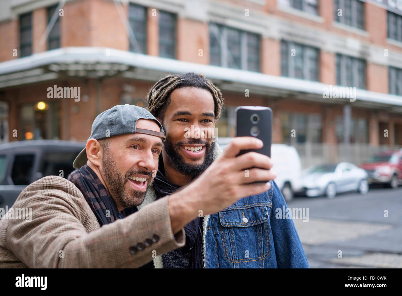 Smiley homosexual couple taking selfie with smart phone in street Stock Photo