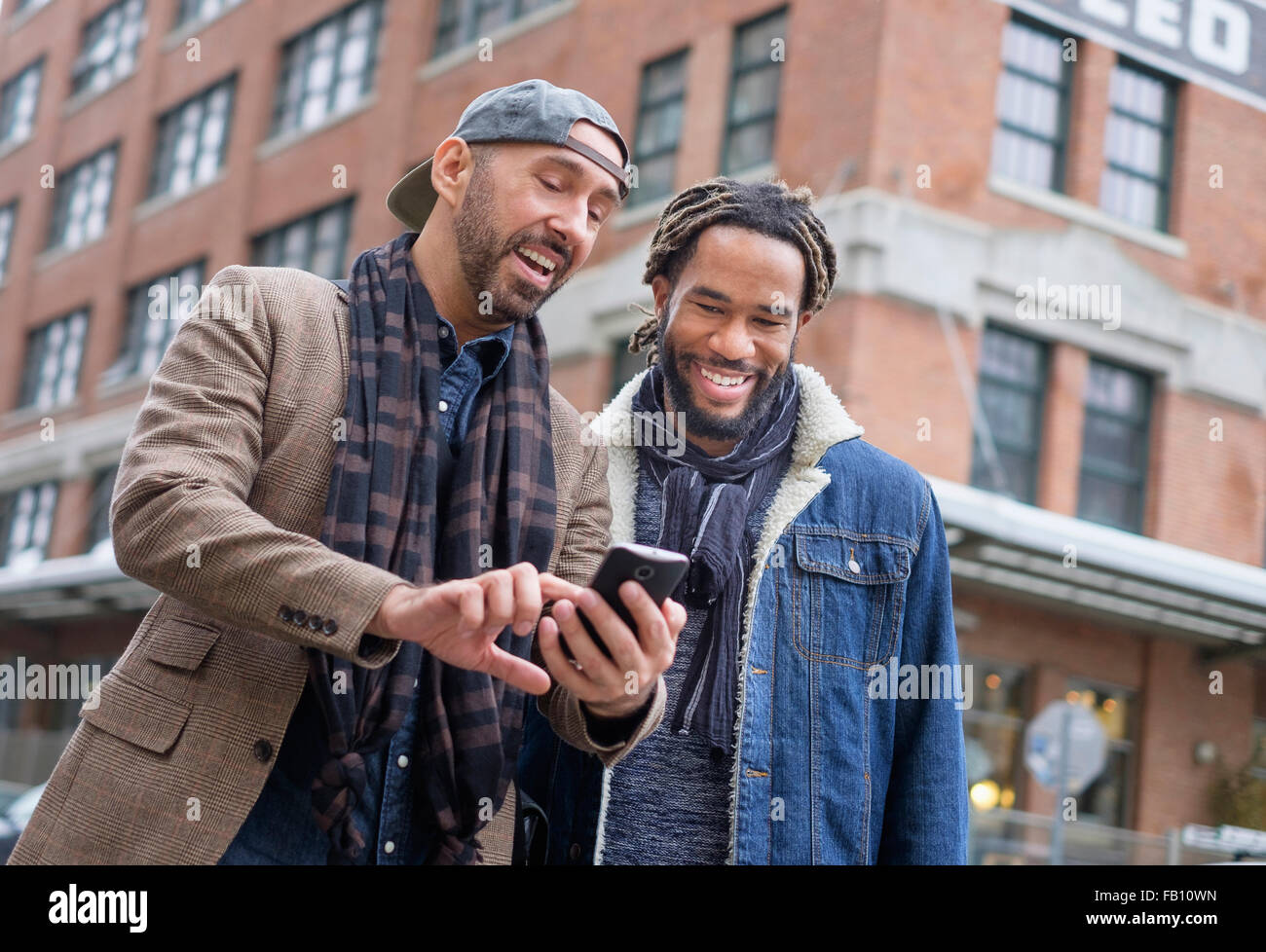 Smiley homosexual couple looking at smart phone in street Stock Photo