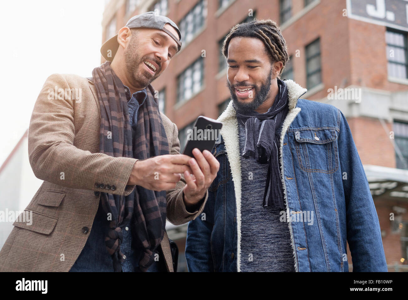 Smiley homosexual couple taking selfie with smart phone in streetStock Photo