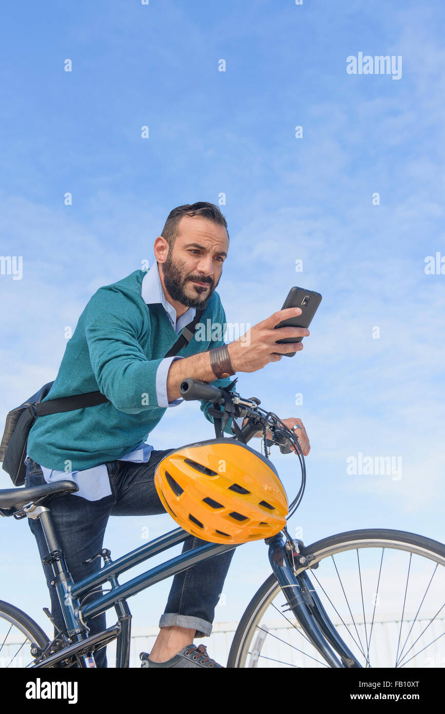 Man with bike using phone - Stock Image