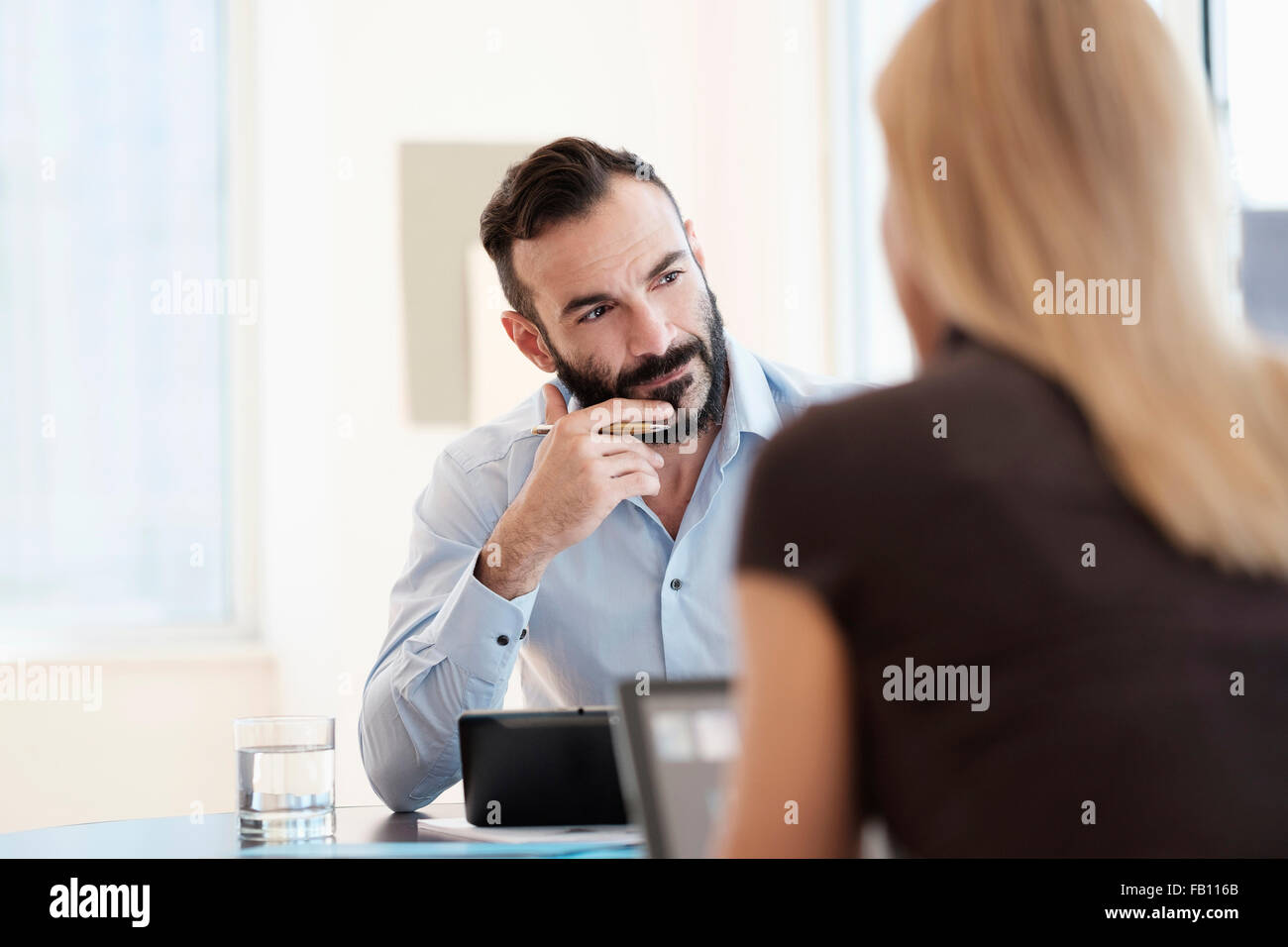 Man and woman sitting in office - Stock Image
