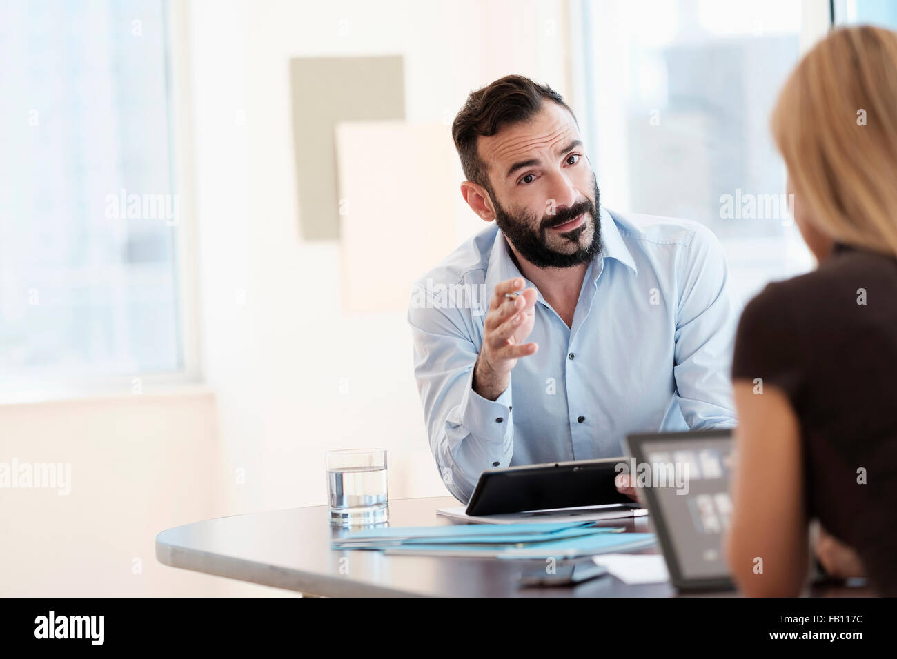 Man and woman talking in office - Stock Image