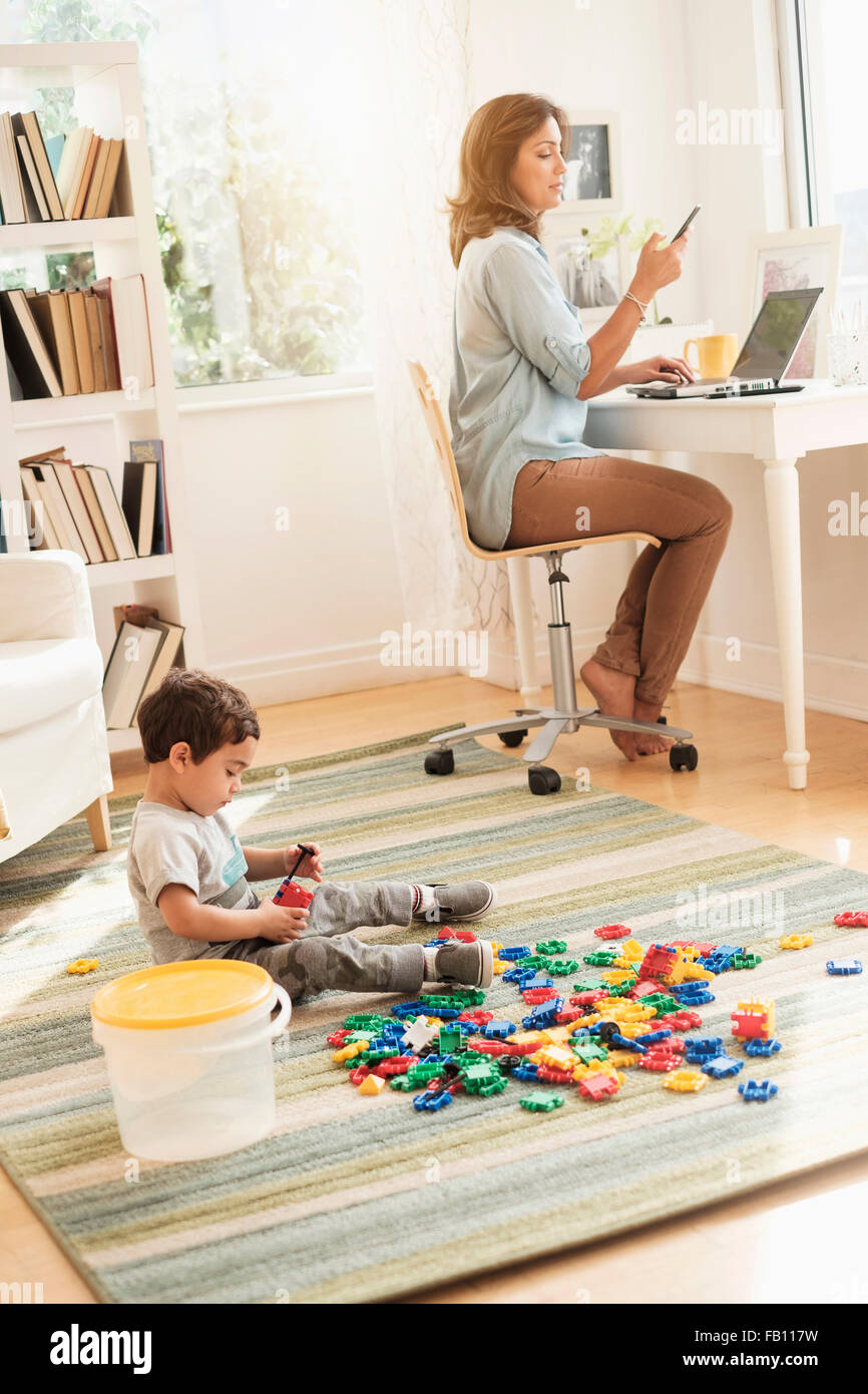 Boy (2-3) playing with toy blocks while mother working on laptop - Stock Image