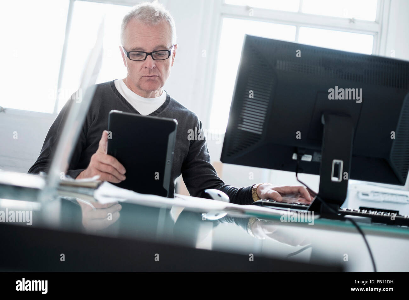 Man working in office using computer and tablet - Stock Image