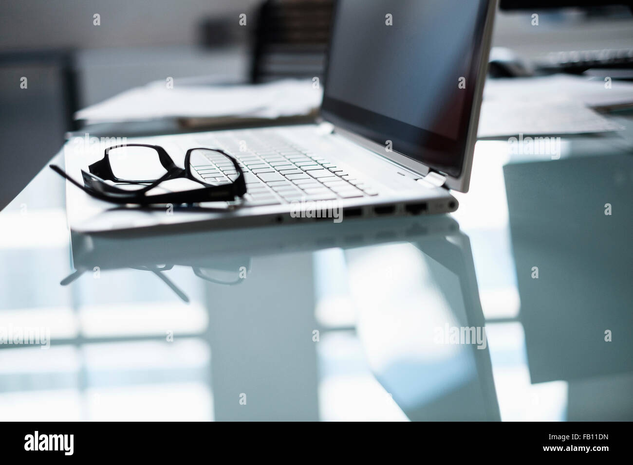 Eyeglasses and laptop on desk in office - Stock Image