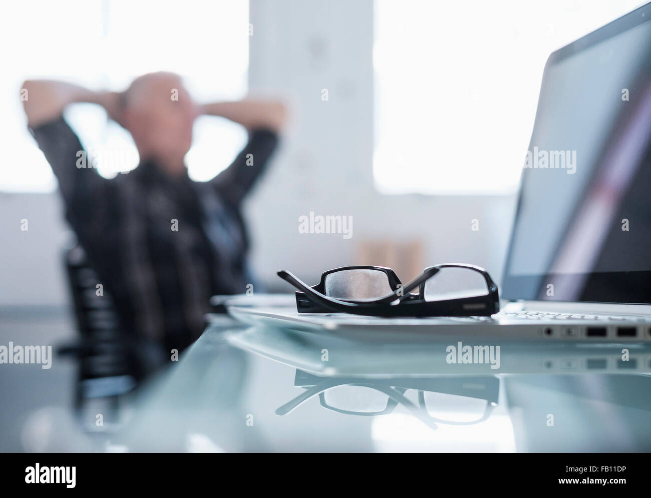 Eyeglasses and laptop on desk in office, man relaxing in background - Stock Image