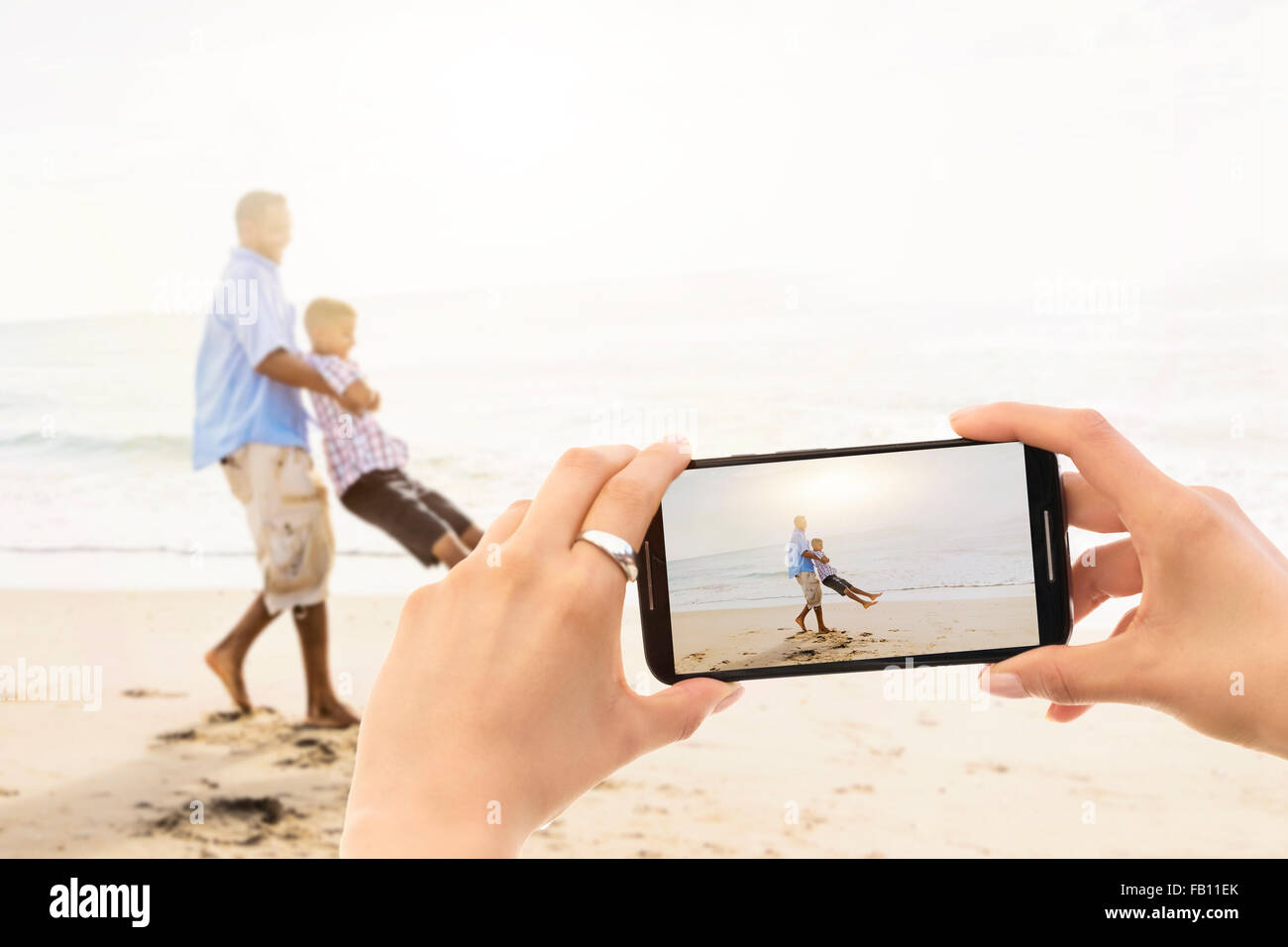 Young woman photographing father with son (12-13) on beach - Stock Image