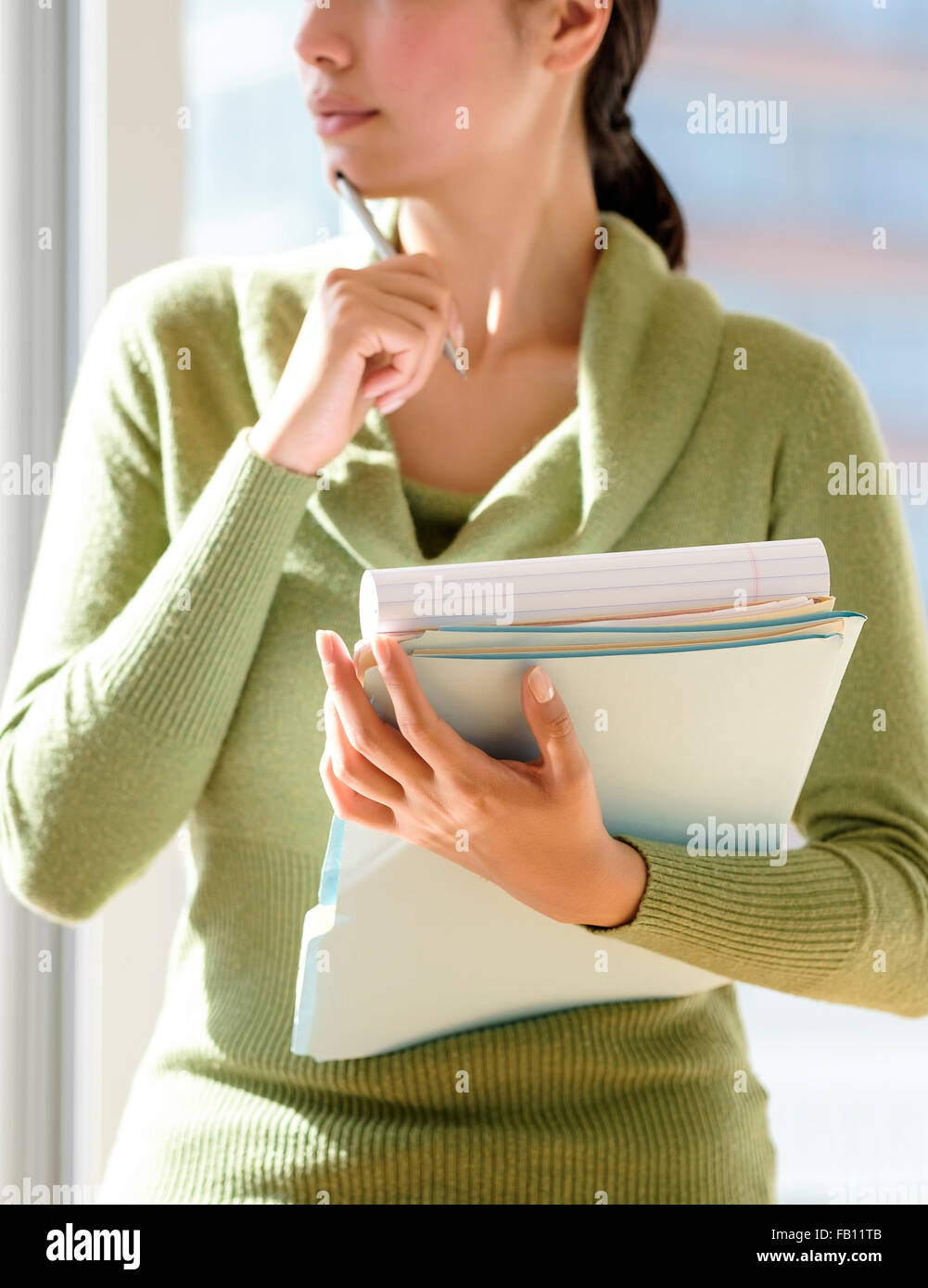 Mid section of business woman holding documents - Stock Image