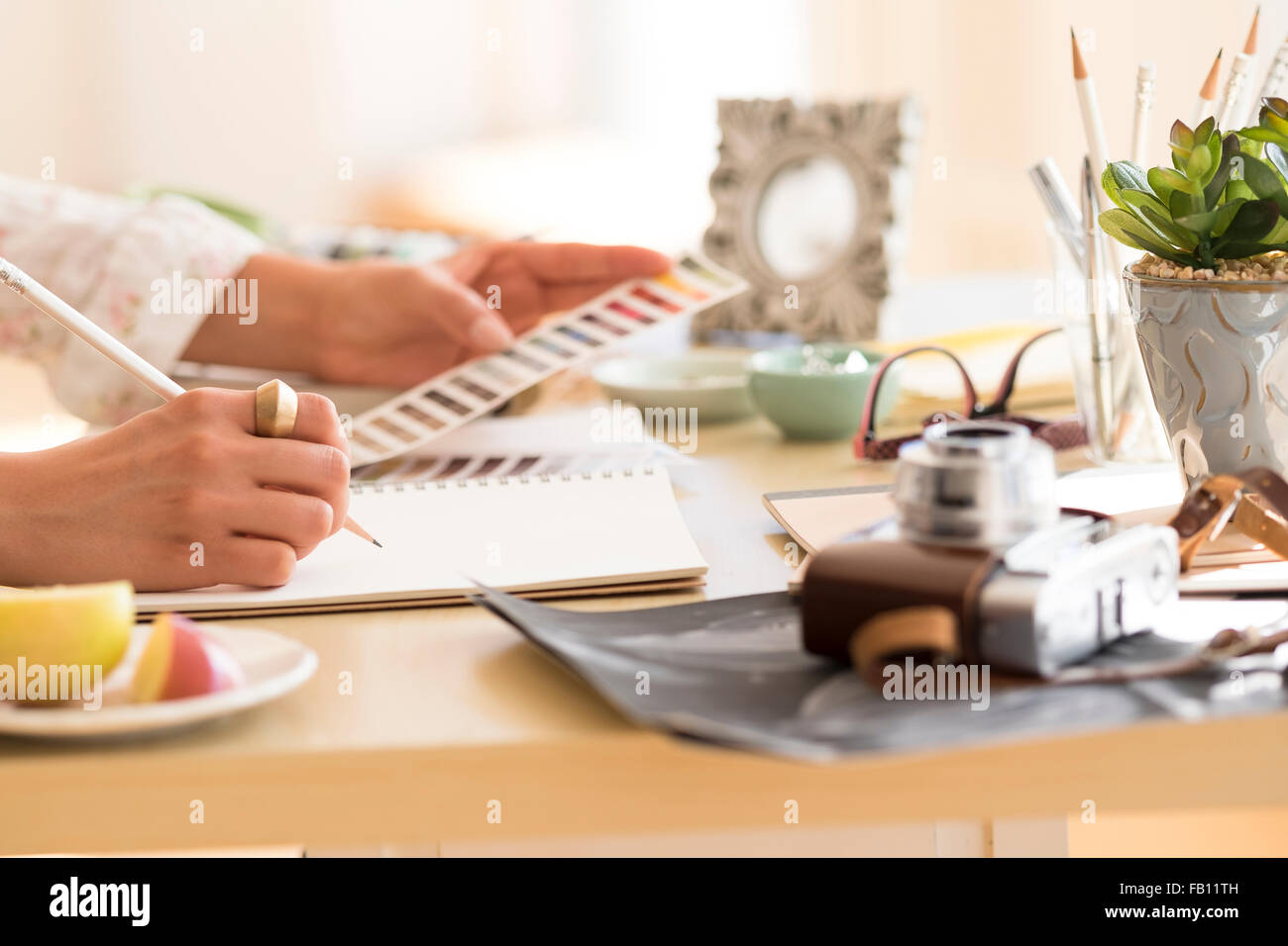 Young woman writing in note pad - Stock Image