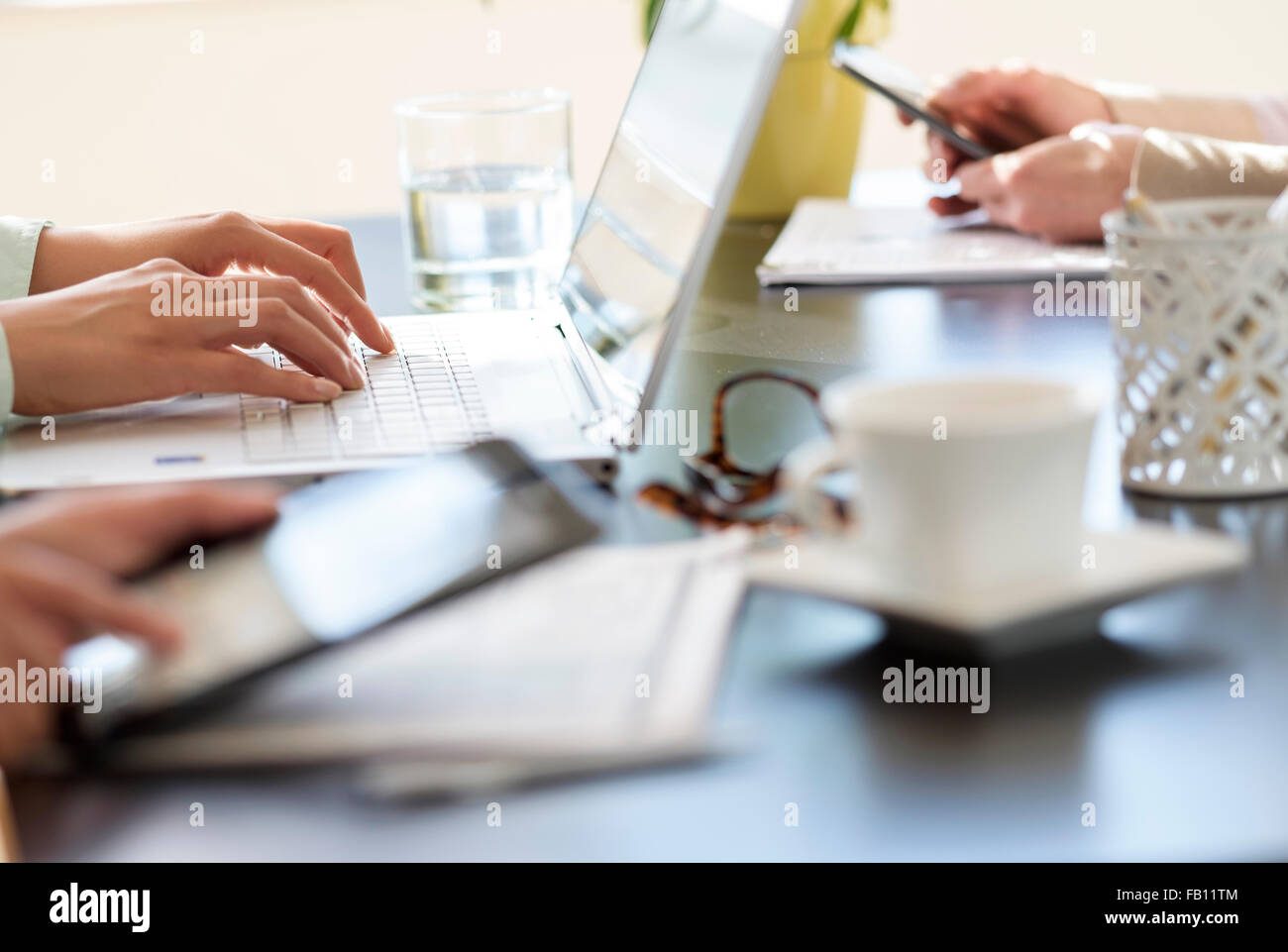 Hands using tablet pc, laptop and smart phone - Stock Image