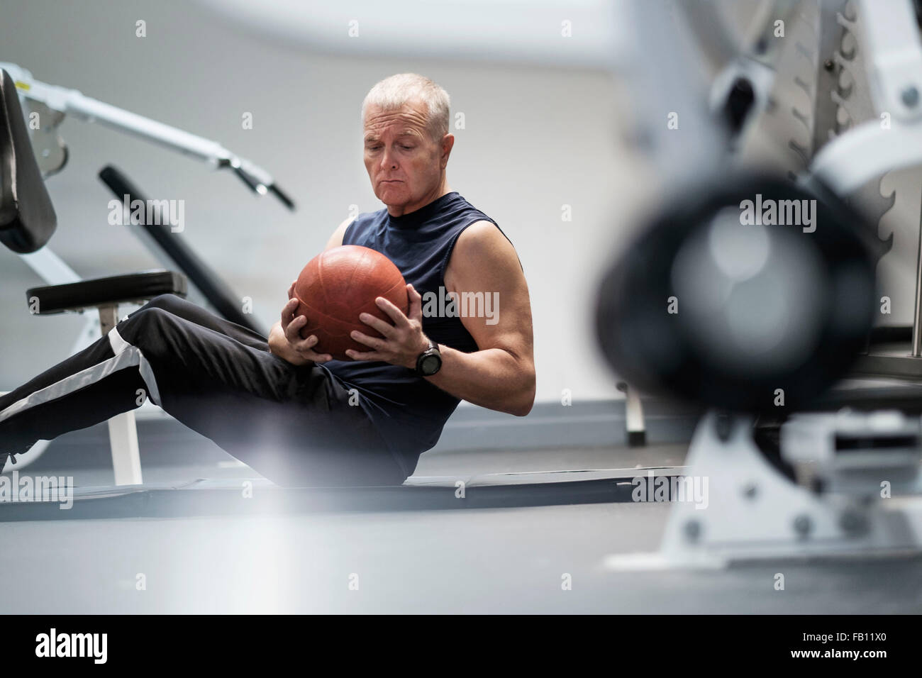 Man in health club exercising with ball - Stock Image