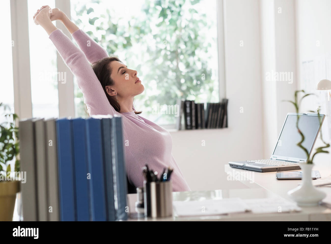 Young woman stretching by desk - Stock Image