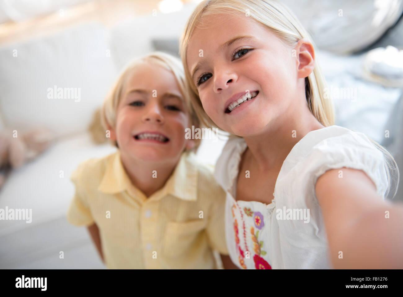 Girl (6-7) and boy (4-5) looking at camera - Stock Image
