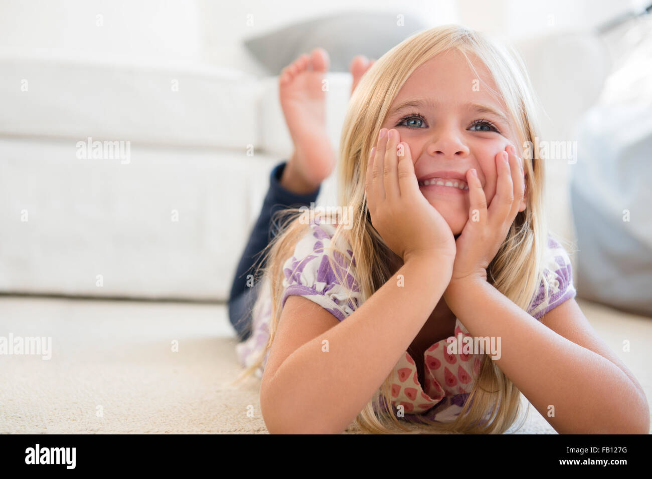Girl (6-7) lying on floor - Stock Image