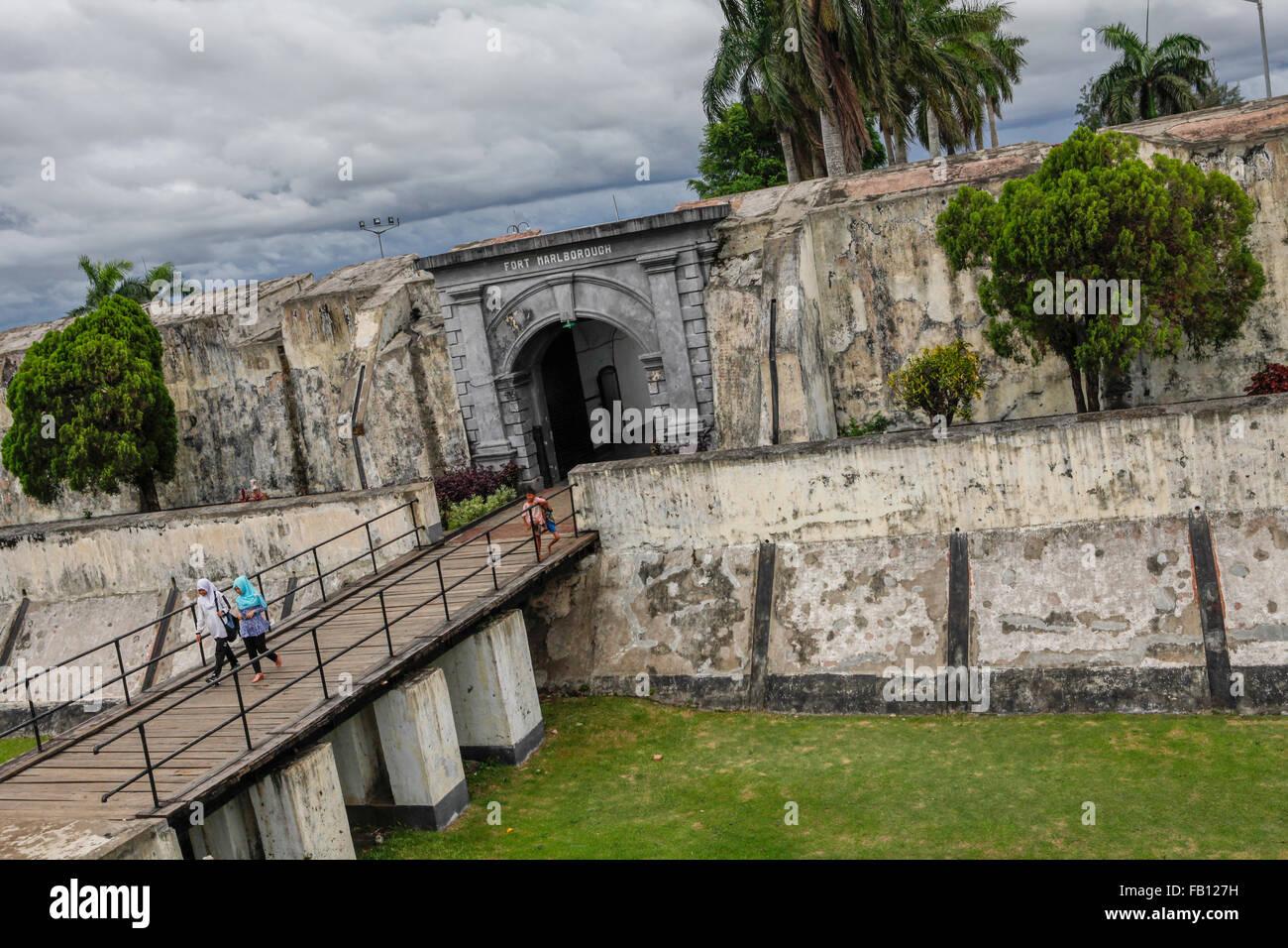 Local tourists walk on the bridge above the moat of Fort Marlborough in Bengkulu, Sumatra. - Stock Image