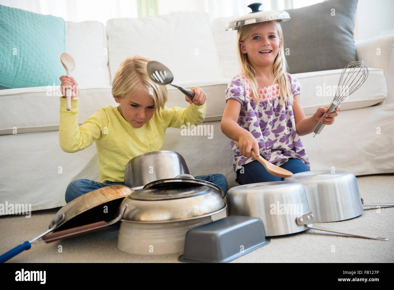 Boy (4-5) and girl (6-7) playing on pots on living room - Stock Image
