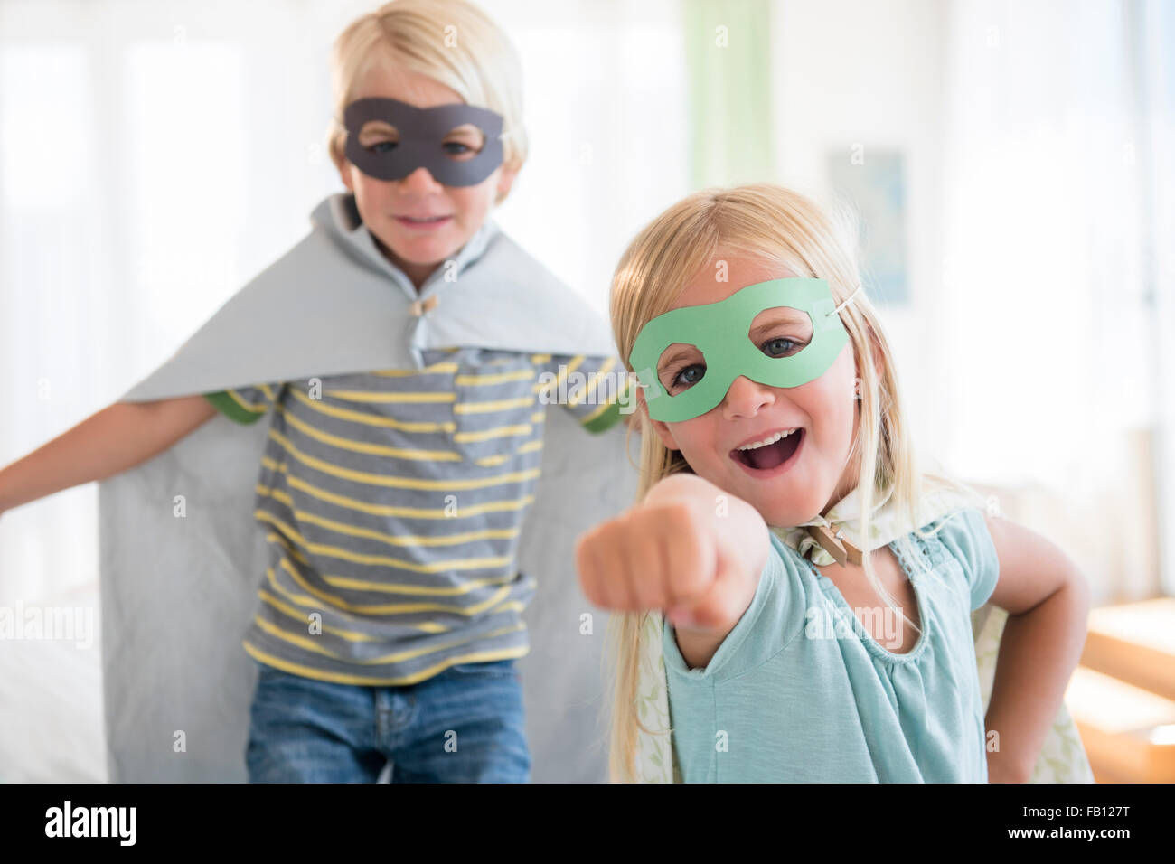 Boy (4-5) and girl (6-7) wearing masks - Stock Image