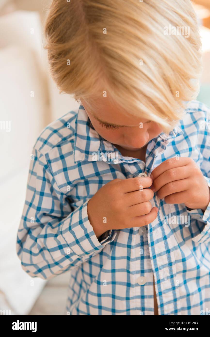 Boy (4-5) buttoning shirt - Stock Image