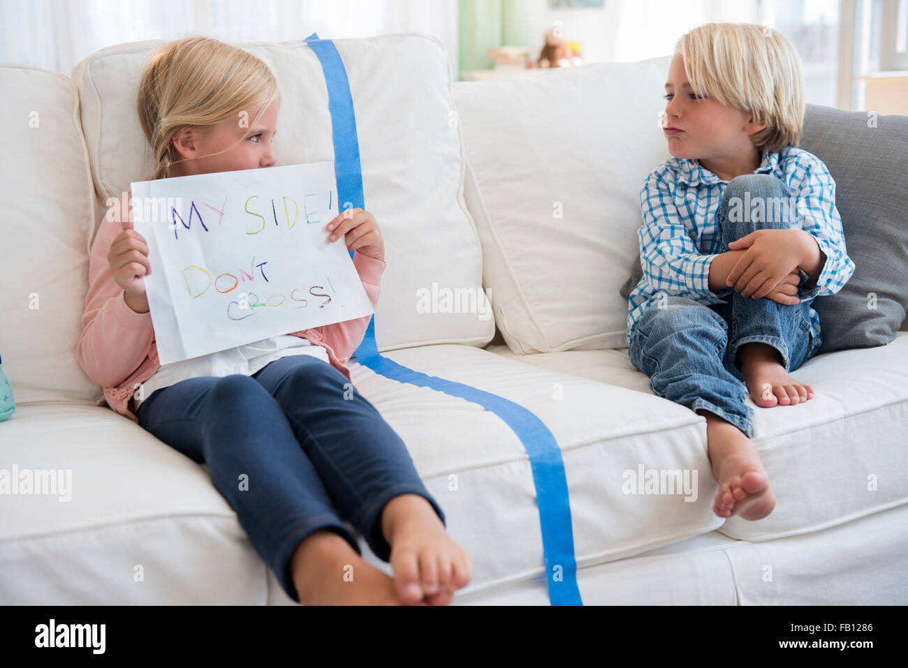 Boy (4-5) sitting on sofa with girl (6-7) holding paper - Stock Image