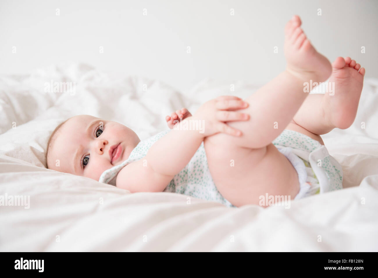 Baby girl (12-17 months) lying down on bed - Stock Image