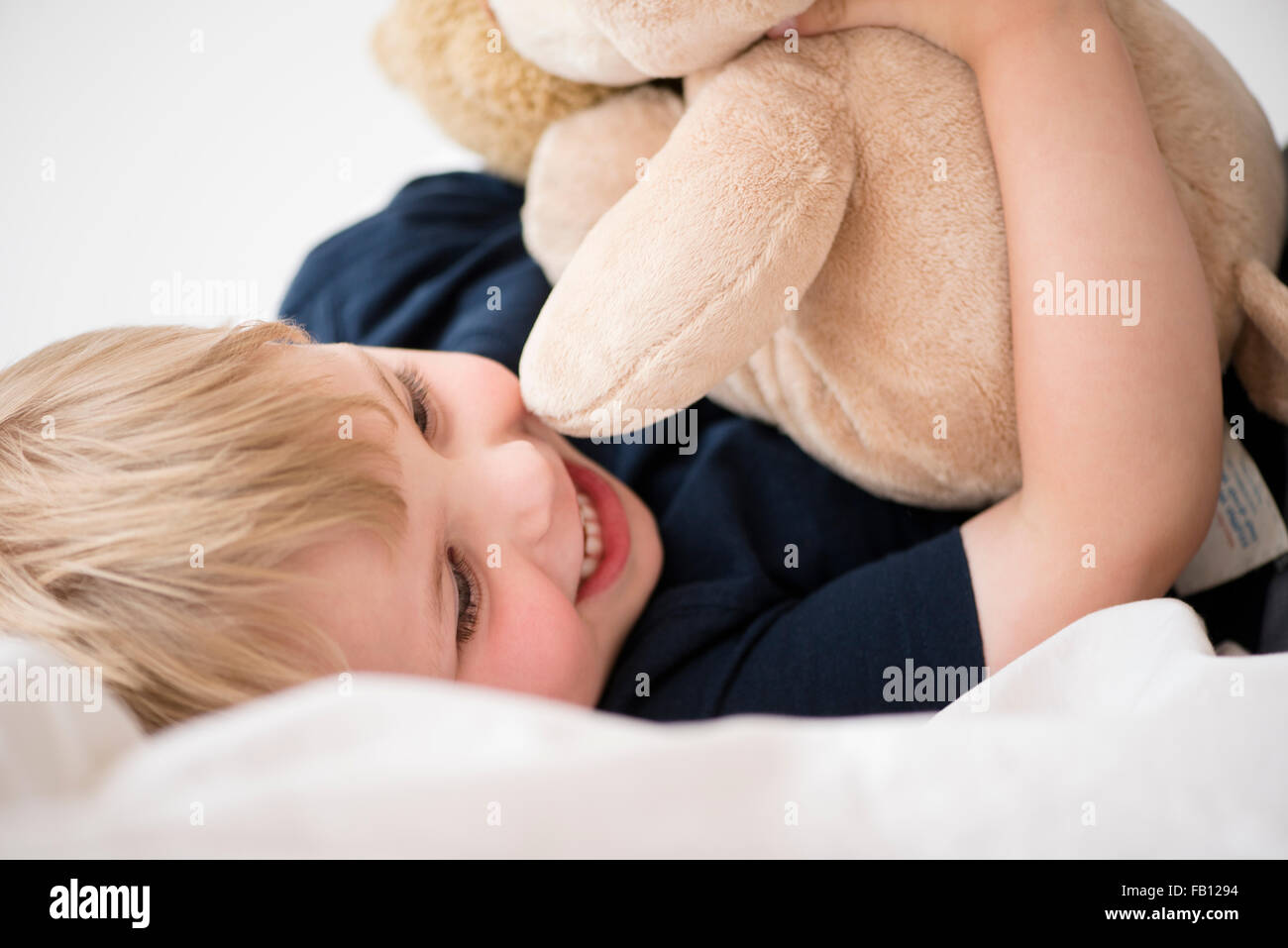 Smiling boy (2-3) with toy lying down on bed - Stock Image
