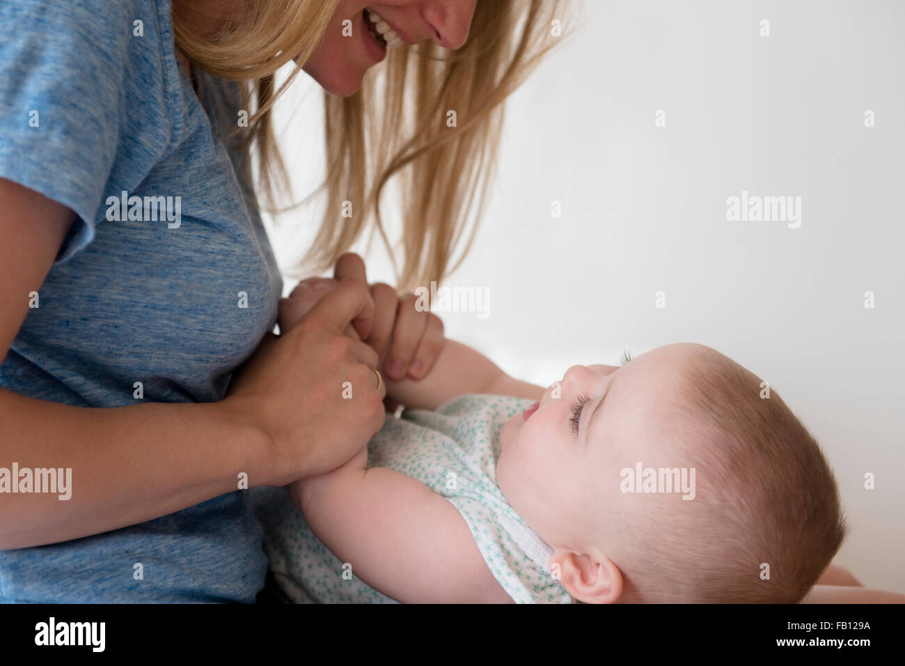 Mother holding hands of baby daughter (12-17 months) - Stock Image