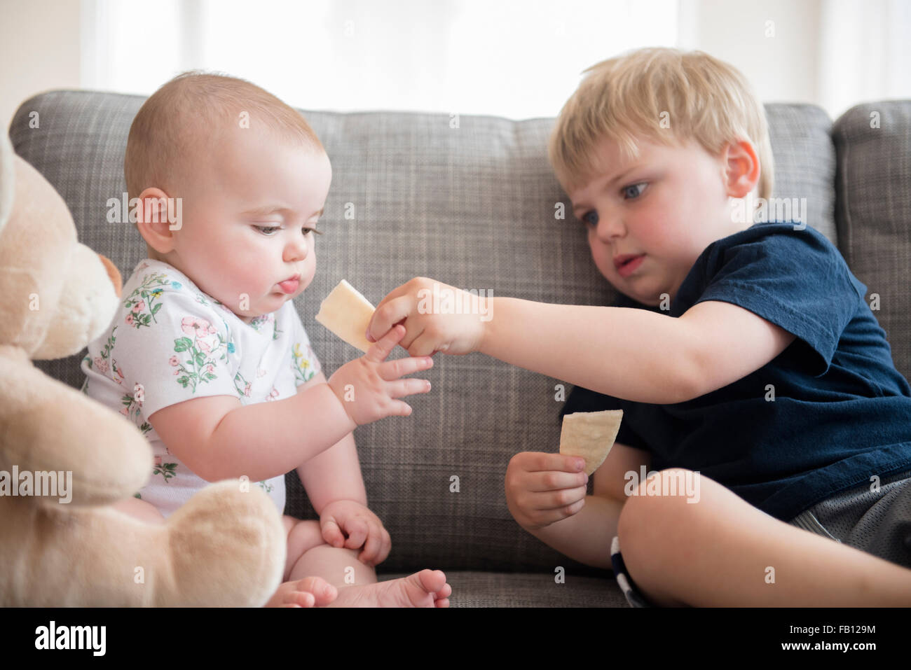Brother (2-3) sharing crackers with baby sister (12-17 months) - Stock Image