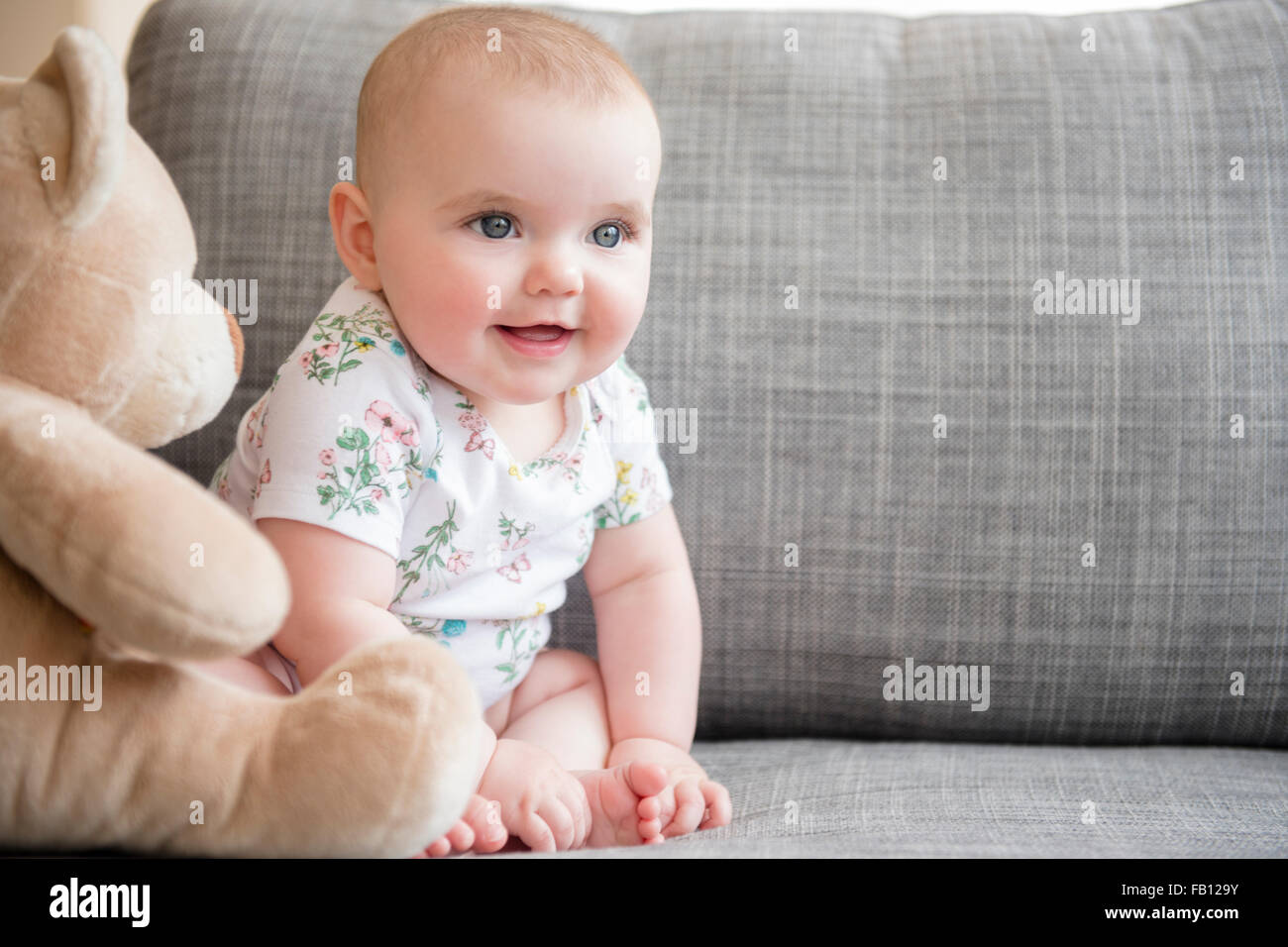 Baby girl (12-17 months) with teddy bear sitting on sofa - Stock Image