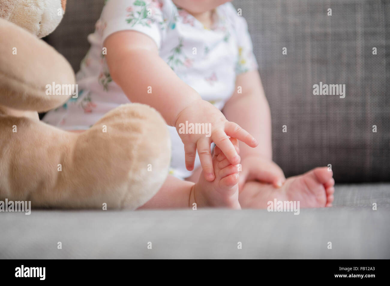 Baby girl (12-17 months) holding foot - Stock Image
