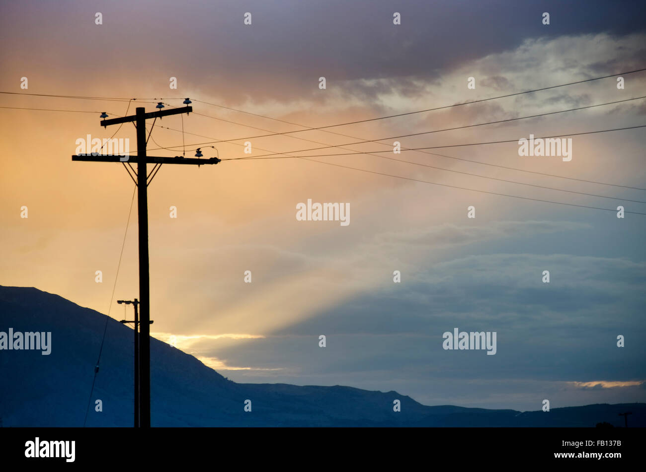 Silhouette of electricity pylon against cloudy sky - Stock Image