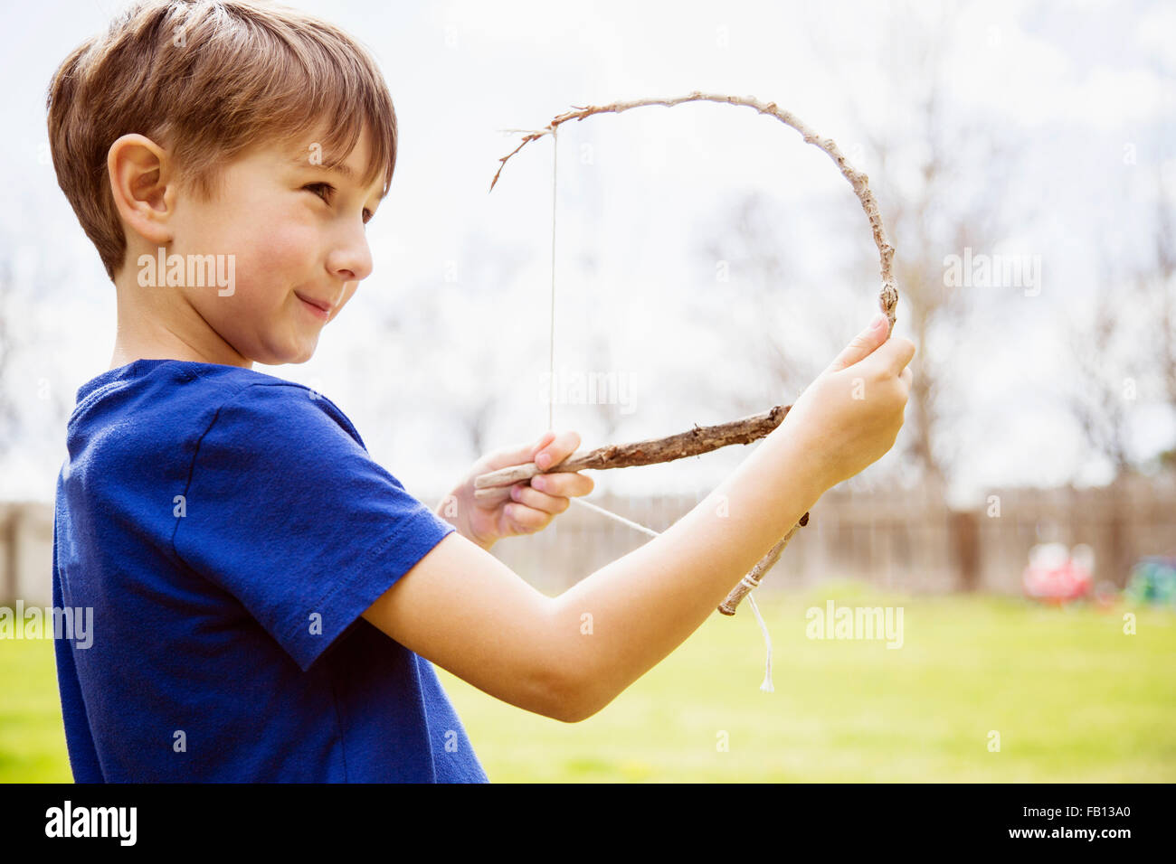 Portrait of boy (6-7) with toy bow - Stock Image