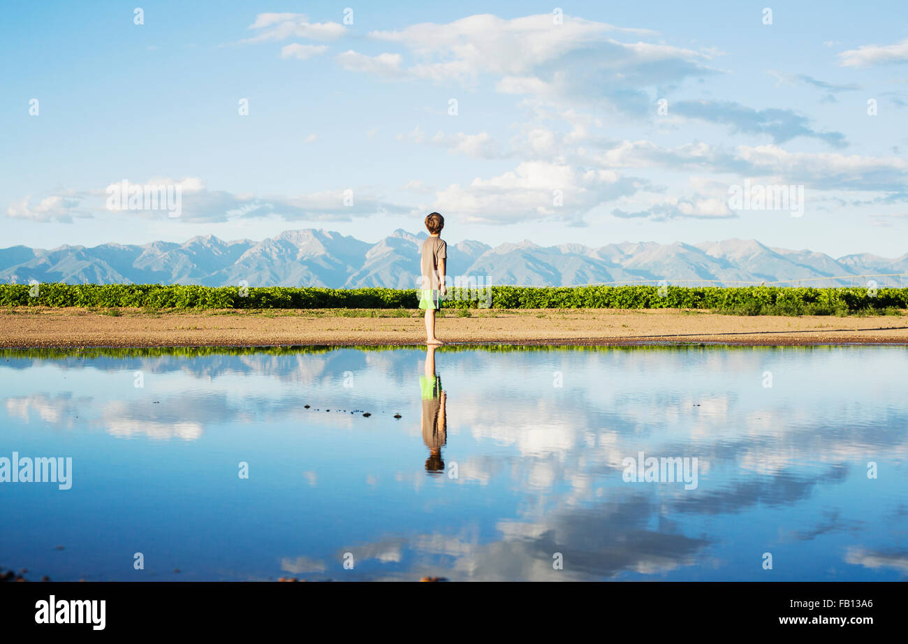 Boy (6-7) standing at water's edge - Stock Image