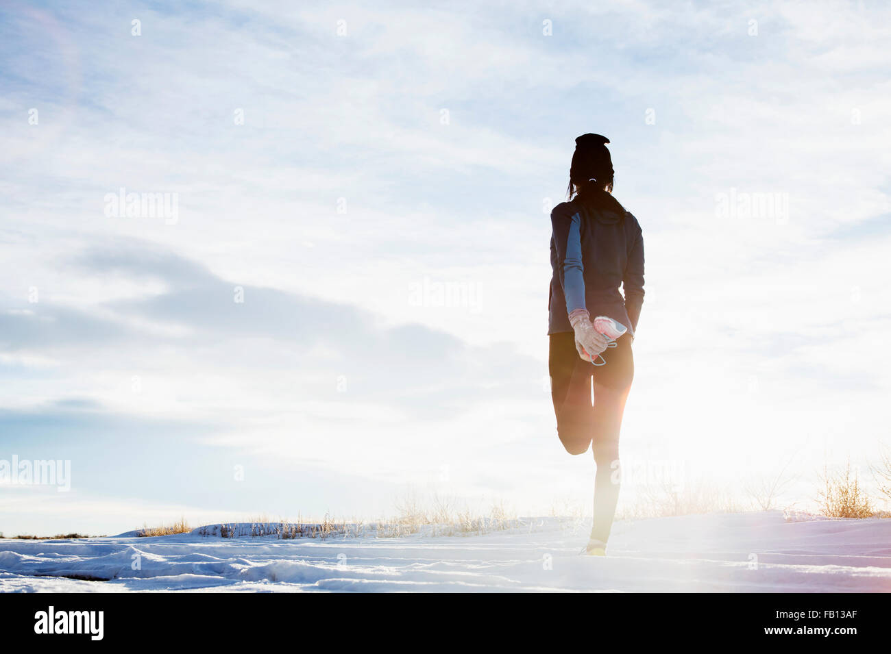 Mature woman stretching in snow - Stock Image