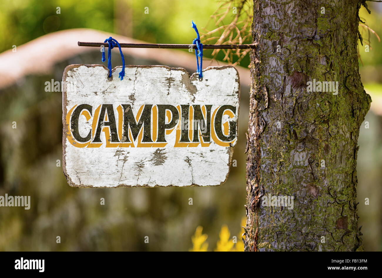 A faded sign advertises a countryside camping ground. Stock Photo