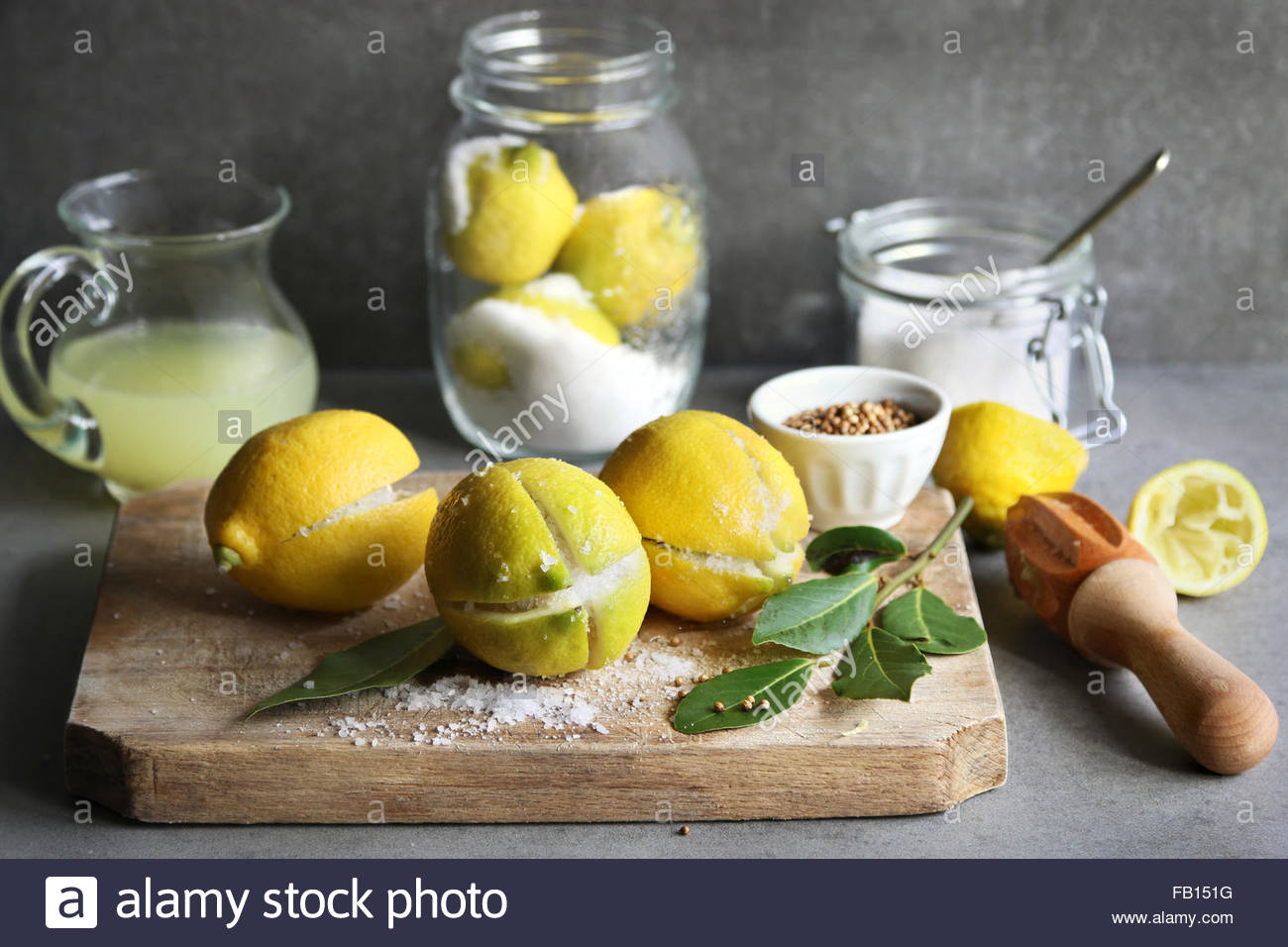 Preserved lemons with salt on a wooden board with a jar of lemon juice and spices on background - Stock Image