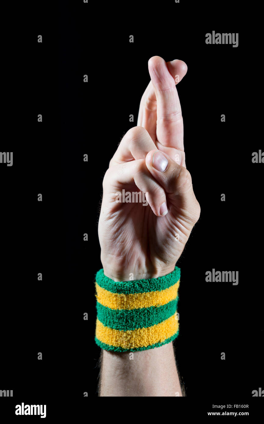 Good luck fingers crossed on hand of an athlete with Brazil colors wristband on black background - Stock Image