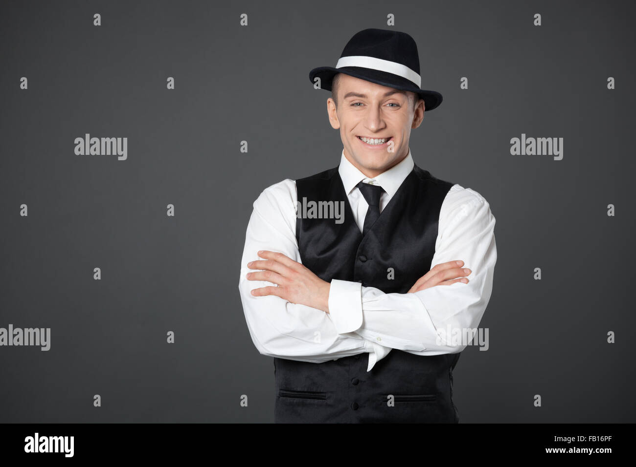 Young male confident male posing in gangster style suite. Studio isolated on gray background. - Stock Image
