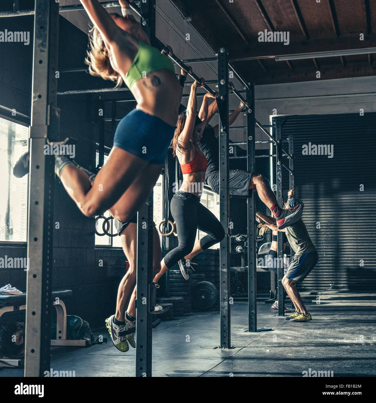 Row of people training on exercise bar in gym - Stock Image