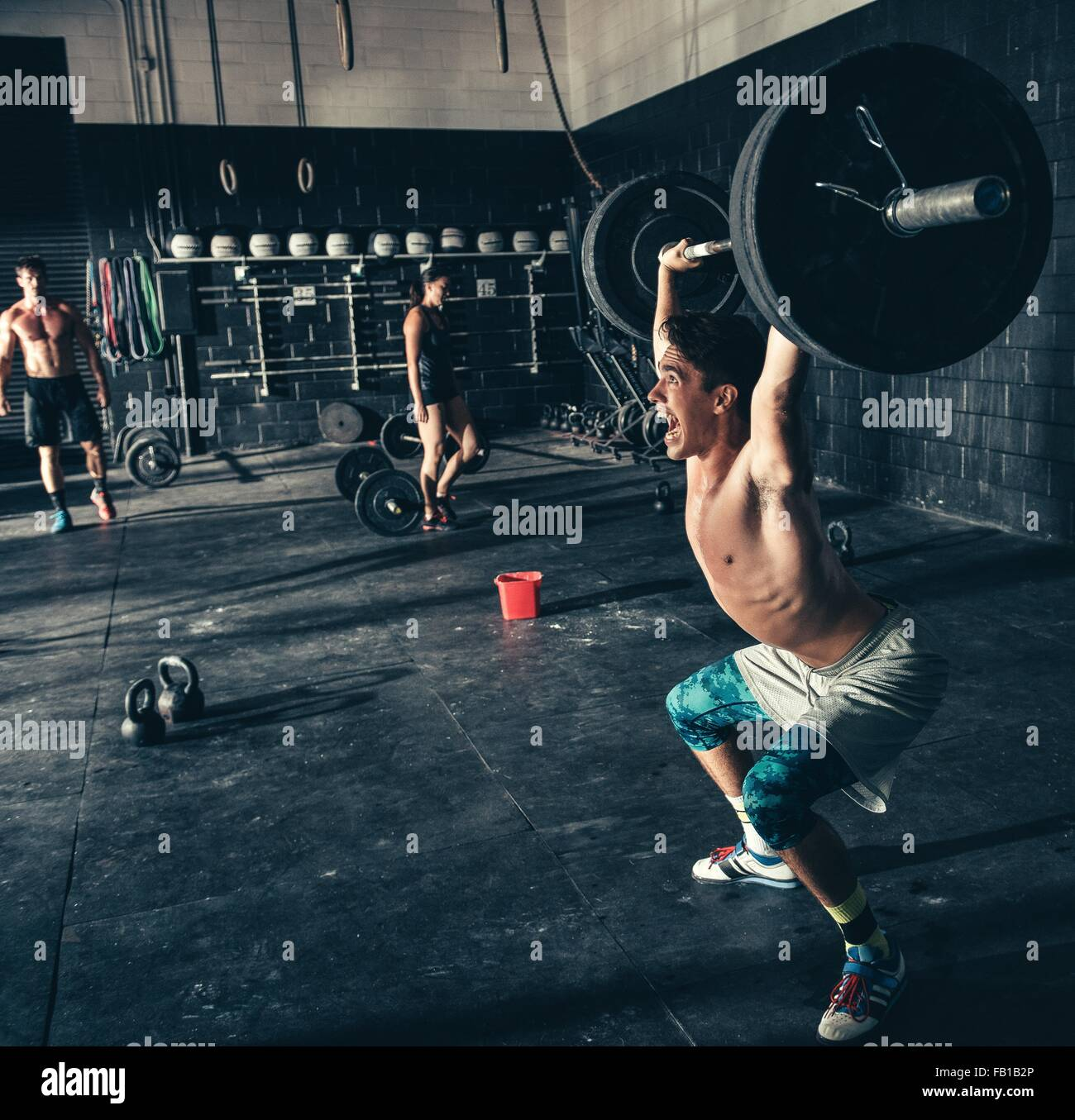 Man shouting whilst lifting barbell in gym - Stock Image