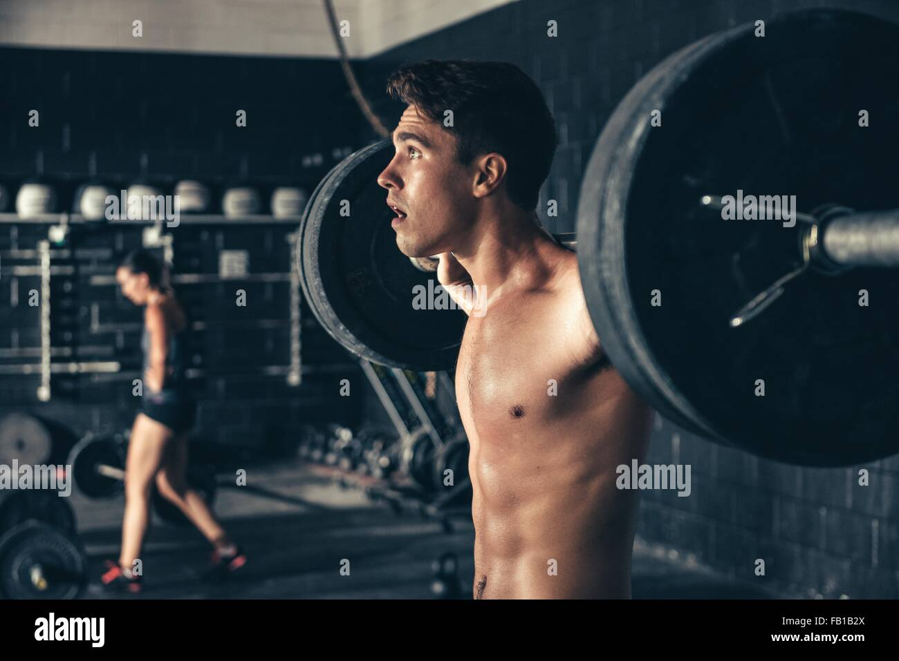 Man lifting barbell on shoulders in gym - Stock Image