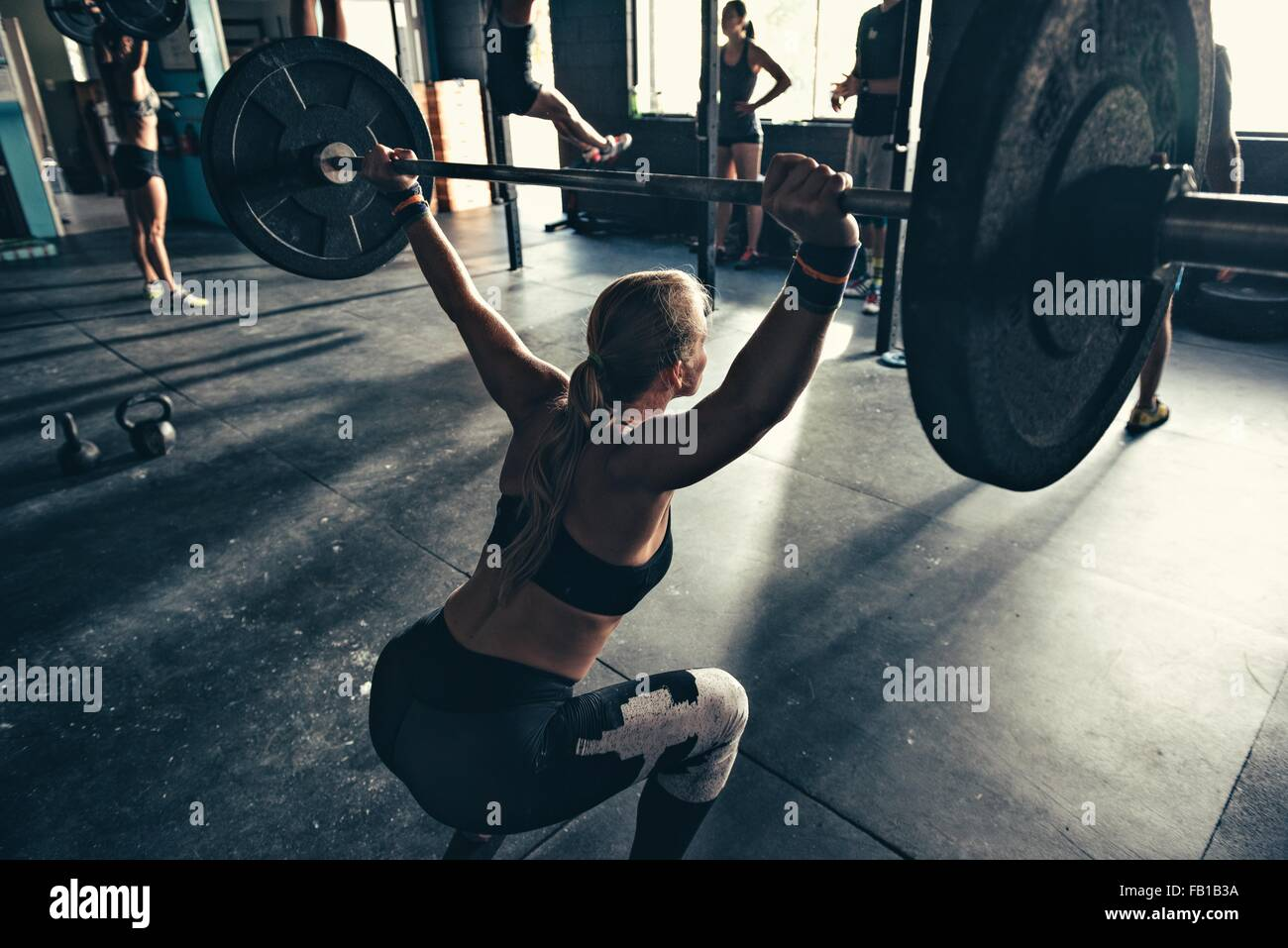 Rear view of woman crouching with barbell in gym - Stock Image