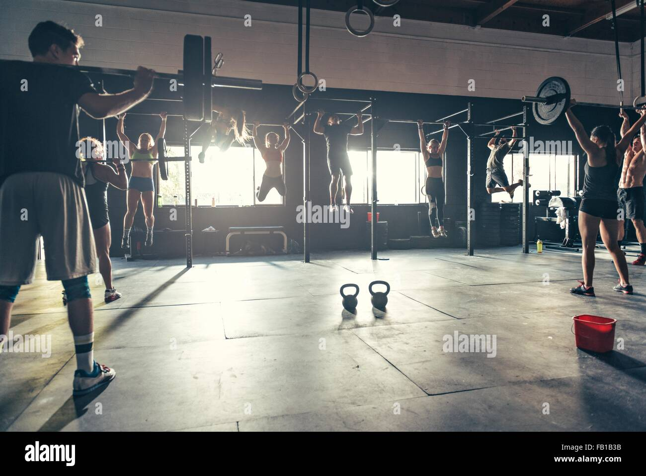 Team training using varied equipment in gym - Stock Image