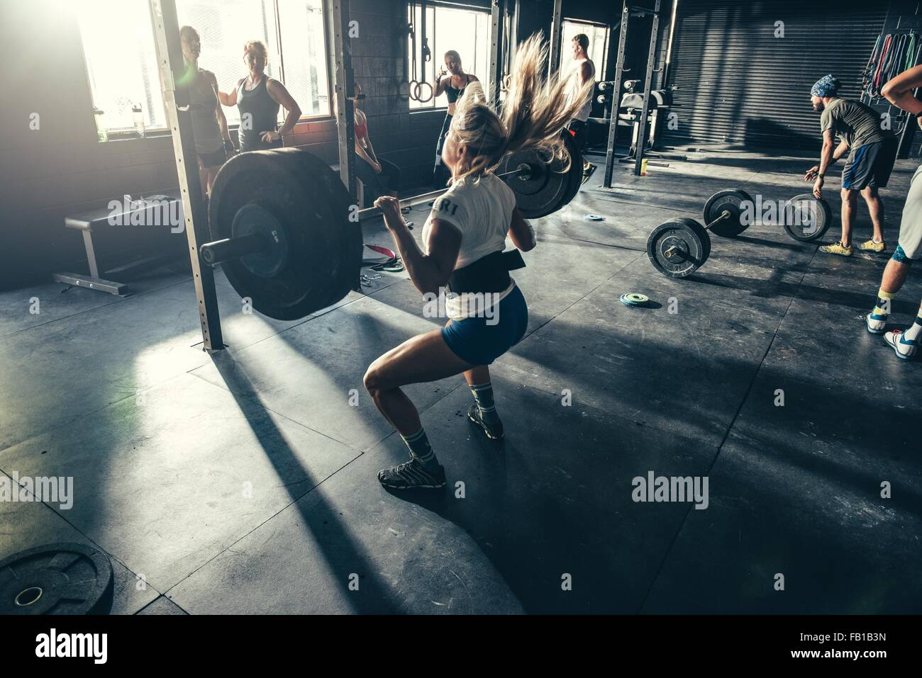 Woman training with barbell in gym Stock Photo