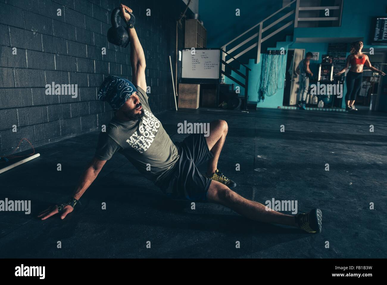 Man lifting kettlebell in  gym - Stock Image