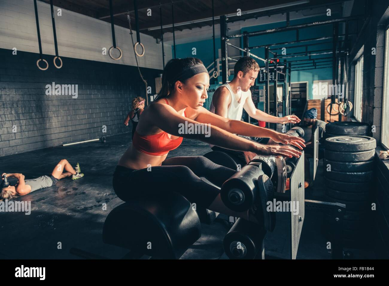 People training on exercise equipment in gym - Stock Image