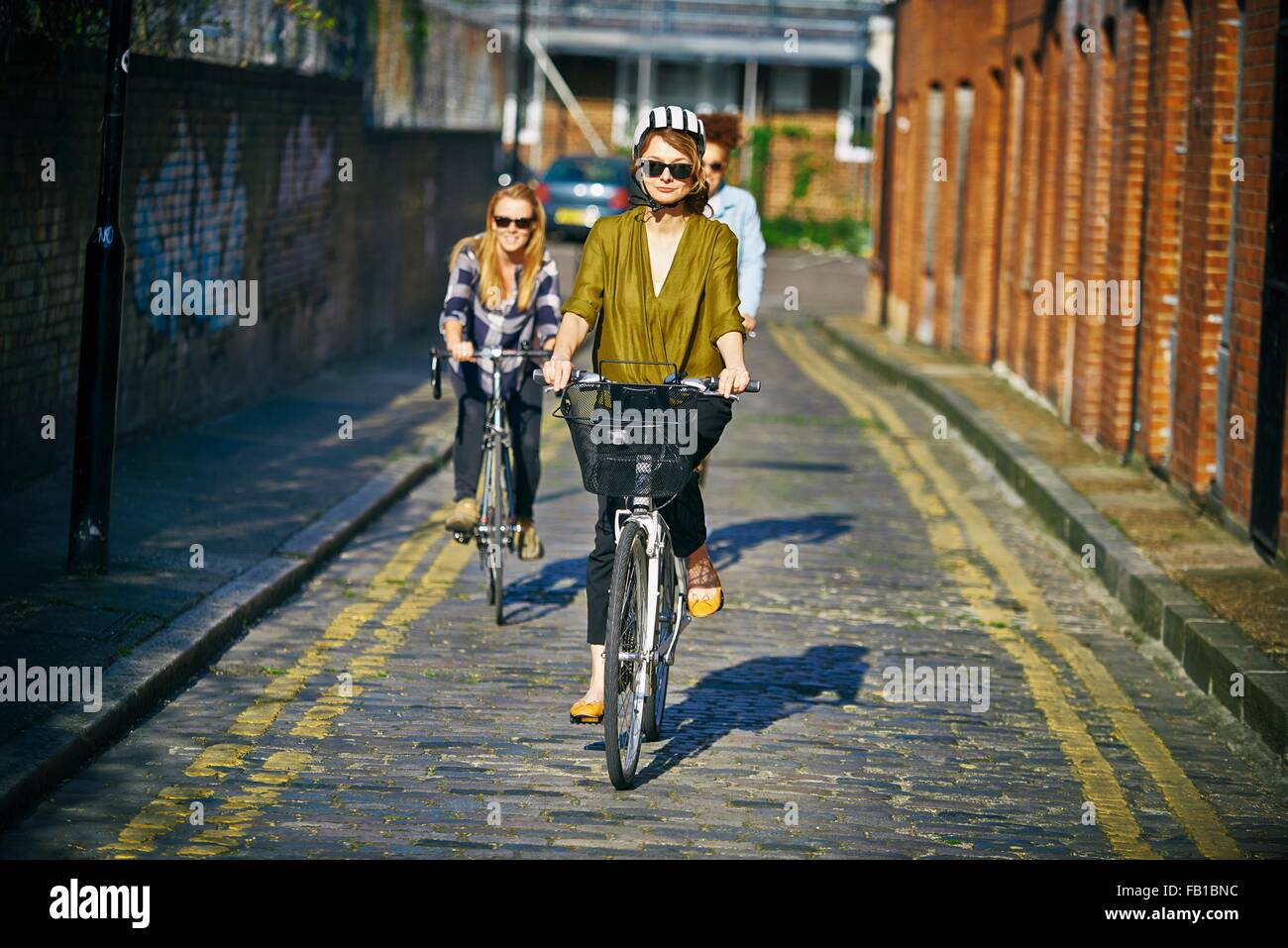 Front view of women wearing sunglasses  riding bicycles on cobblestone road - Stock Image