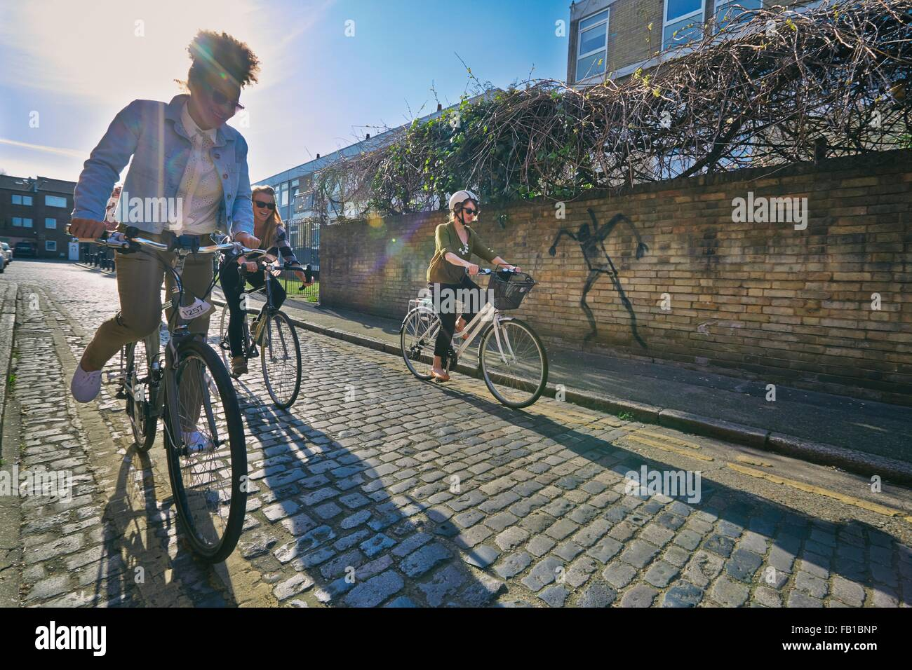 Angled view of women cycling on bicycles on cobblestone road - Stock Image