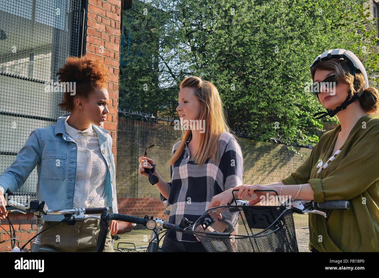 Women in urban area, waist up, standing holding bicycles chatting - Stock Image