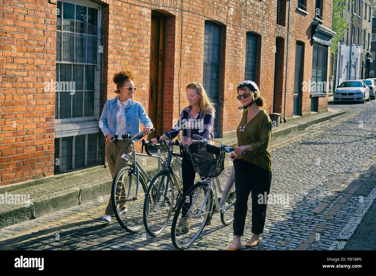 Angled view of women in urban area pushing bicycles on cobblestone road - Stock Image
